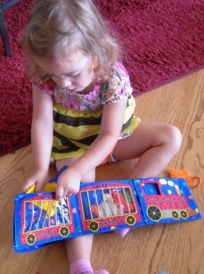 Clara playing with circus train book